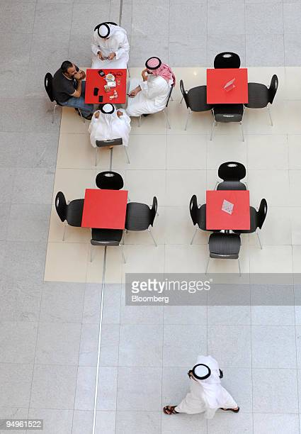 Men sit and drink coffee while visiting the Dubai Mall which is owned by Emaar Properties PJSC in Dubai United Arab Emirates on Sunday July 12 2009...