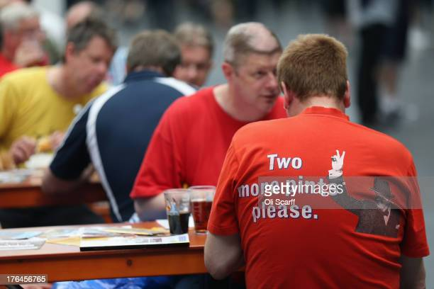Men sit and enjoy their drinks at the Great British Beer Festival in the Olympia exhibition centre on August 13, 2013 in London, England. The...