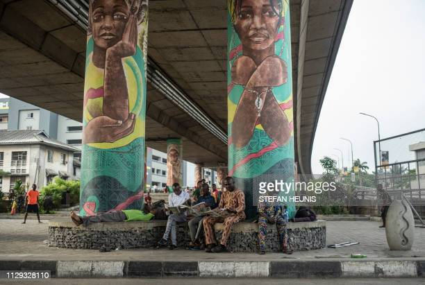 Men sit and read the morning papers under a bridge in Lagos ahead of the local election voting day on March 9 2019 Nigerians are voting for a second...
