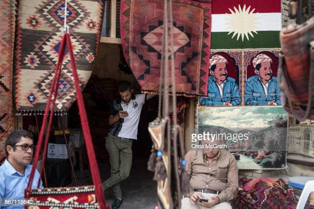 Men sit around at a rug store underneath a portrait of Kurdistan President Massud Barzani in the old city on October 27 2017 in Erbil Iraq After the...