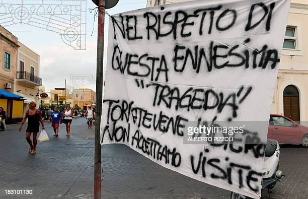 Men sit in front of a banner reading In respect of the latest tragedy go back we don't accept visits on October 4 2013 in Lampedusa Italy mourned...
