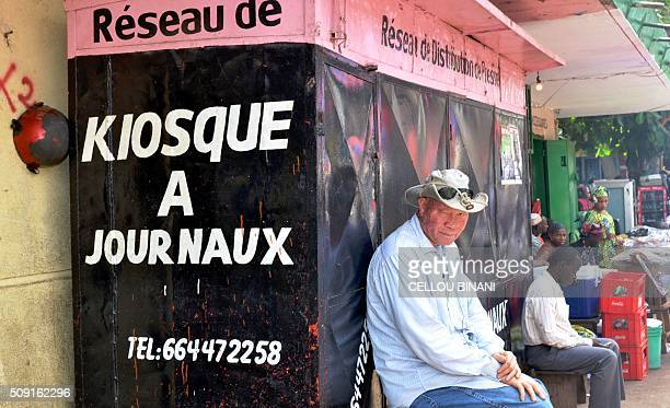 Men sit in front of a closed newspaper stand in Conakry on February 9 on a 'pressfree day' in honour of a journalist who was shot dead last week Five...