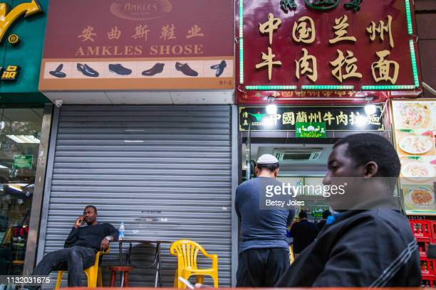 Men sit in front of a restaurant off Little North Road, part of an ethnically diverse quarter in Guangzhou known as Little Africa on February 3, 2019...