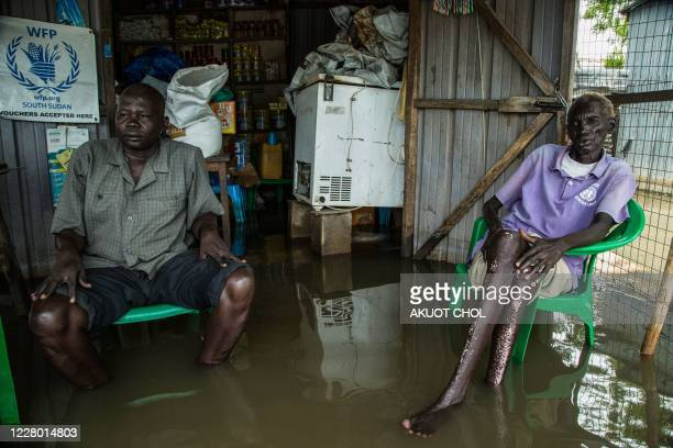 Men sit inside a flooded shop in a flooded area after the Nile river overflowed after continuous heavy rain which caused thousands of people to be...