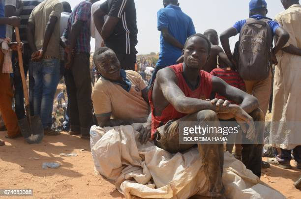 Men sit on a bag as hundreds of people search gold on April 25 2017 in KafaKoira south of Niamey Hundreds of people sometimes whole families rush to...