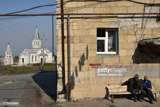 Men sit on a bench in front of residential building not far from the damaged Ghazanchetsots Cathedral in the historic city of Shusha, some 15...