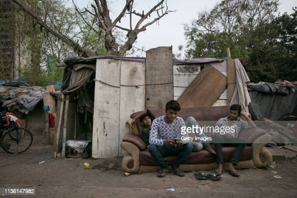 Men sit on a couch in a slum on April 7 2019 in New Delhi India With a rising number of jobless youths unemployment and poverty have been at the top...