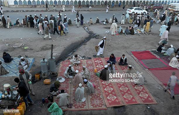 Men sit on carpets to drink tea and eat sugar bread in the early morning in Kabul on September 24 2012 Despite massive injections of foreign aid...