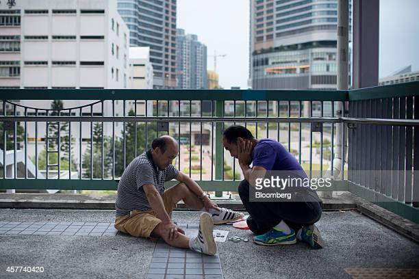 Men sit playing checkers on a pedestrian overpass in the Tseung Kwan O district of Hong Kong China on Thursday Oct 23 2014 Hong Kong is scheduled to...