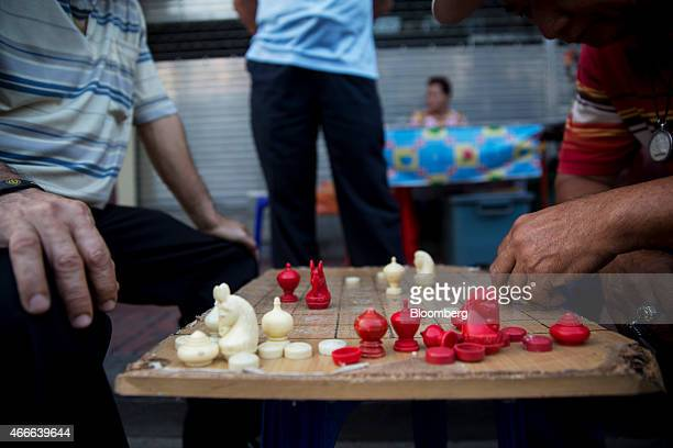 Men sit playing makruk Thai chess in the Chinatown area of Bangkok Thailand on Sunday March 15 2015 Almost a third of Thailand's population will be...