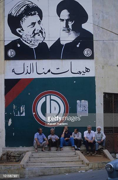Men sit under under a portrait of Ayatollah Khomeini and Imam Musa Sadr in a Amal neighborhood in the southern suburb of Beirut during the civil war,...