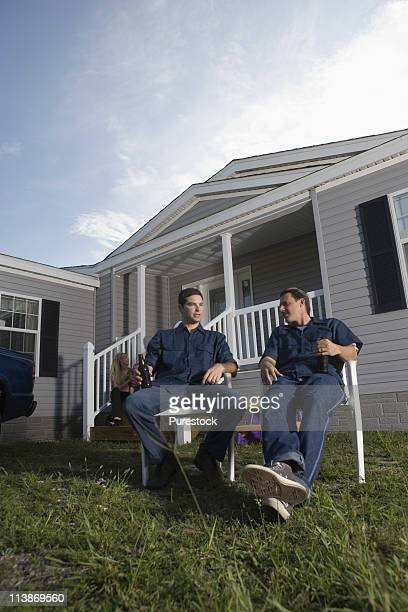 Men sitting and holding drink bottles in front yard of trailer home