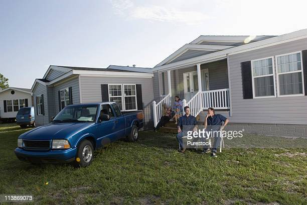 Men sitting and talking in front yard of trailer home