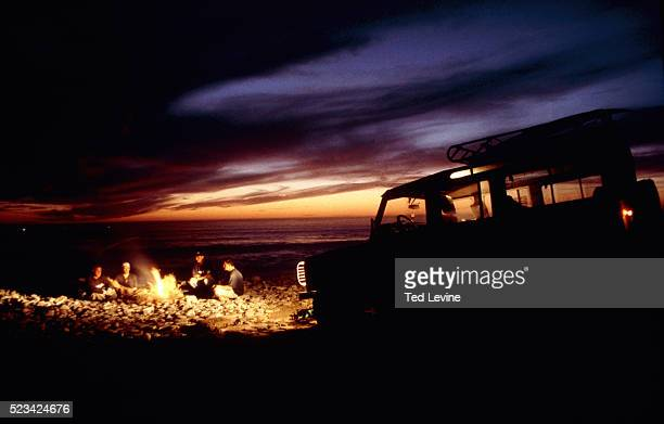 4 men sitting around camp fire on rocky beach, Jeep beside, Tarhazoute, Morocco