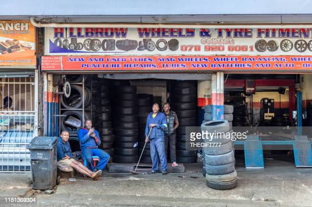 men sitting at a wheel & tyre fitment centre in the streets of hillbrow, johannesburg - gauteng province stock pictures, royalty-free photos & images