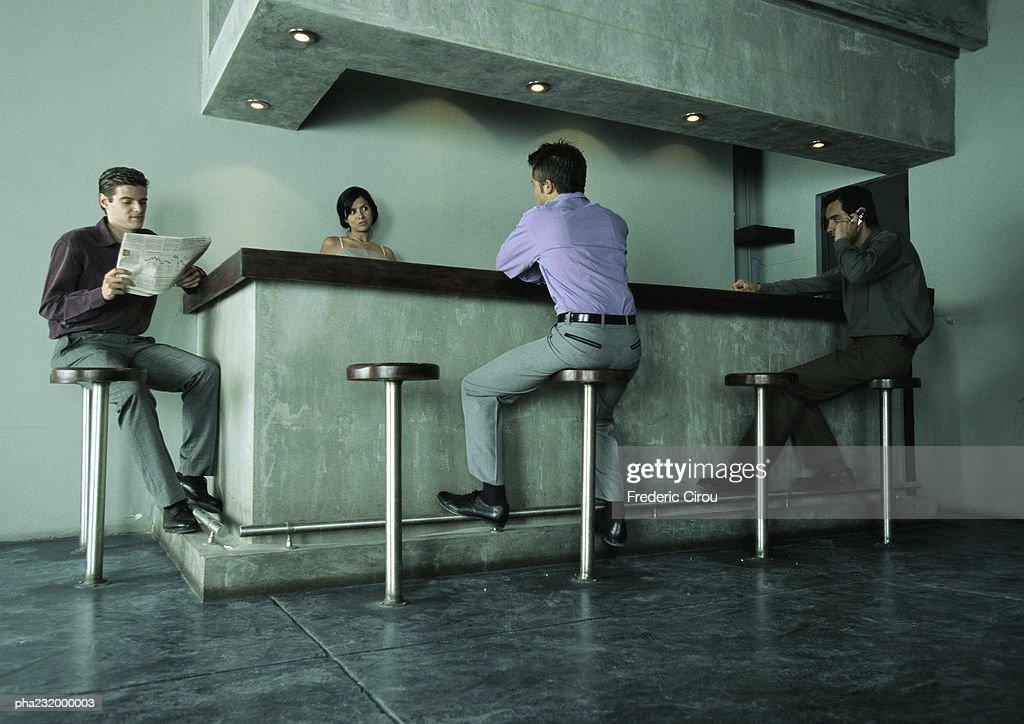 Men sitting at bar, woman standing behind bar. : Stockfoto