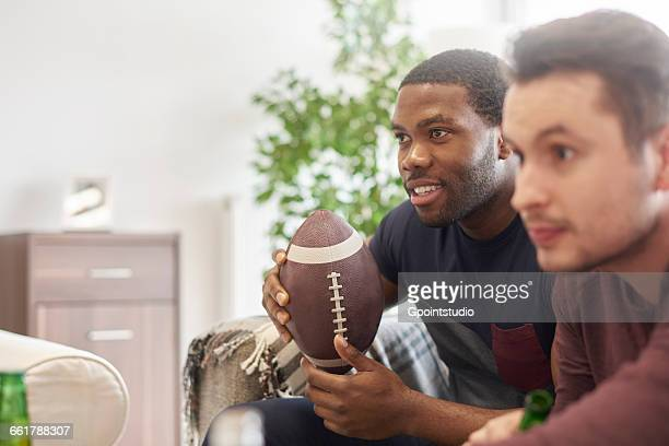 men sitting in lounge holding ball looking away - american football sport stock photos and pictures