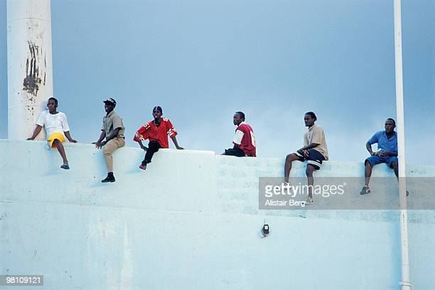 men sitting on a high wall - kingston jamaica stock pictures, royalty-free photos & images