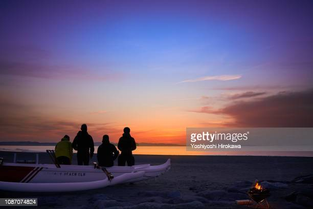 Men sitting on canoe in beach. They waiting for sunrise on the morning glow coast.