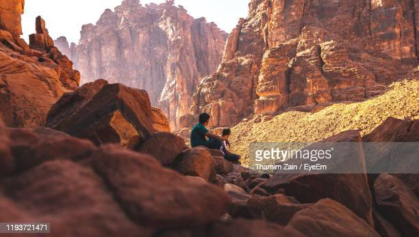 men sitting on rock formation - saudi arabia stock pictures, royalty-free photos & images