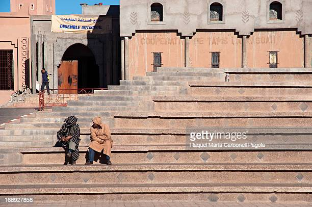 Men sitting on stairs in front of Kasbah Taourirt, Ouarzazate, Morocco, 2012