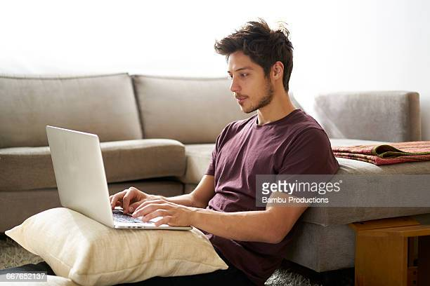 Men sitting on the carpet with laptop