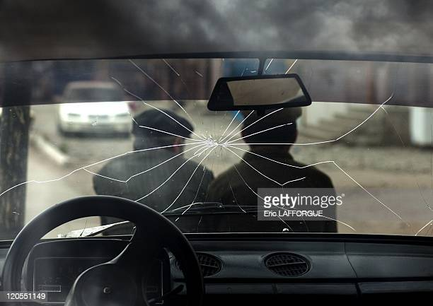 Men Sitting On The Hood Of A Car With A Broken Windscreen in Kochkor, Kyrgyzstan on August 25, 2009 - Kochkor is a town of Naryn Province in northern...