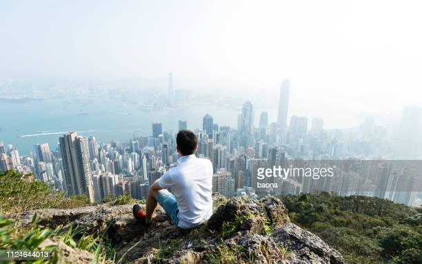 men sitting on the top of mountain and looking cityscape - skyscraper stock pictures, royalty-free photos & images