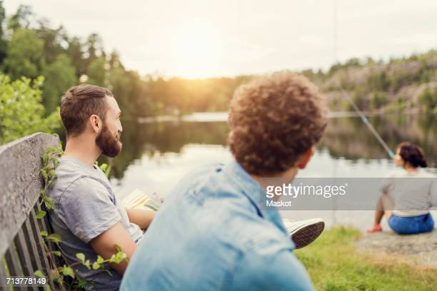 Men sitting on wooden bench while female friend fishing at lakeshore