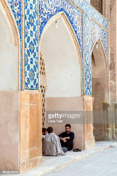 Men sitting under an arch in the Masjede Jame or Friday Mosque in Esfahan Iran