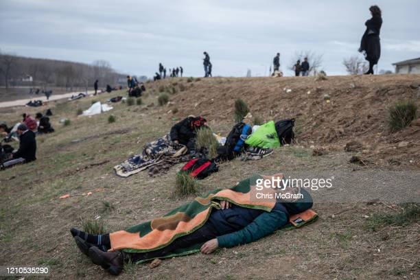 Men sleep at a makeshift camp for refugees and migrants next to the Edirne Old Bridge on March 05 2020 in Edirne Turkey Thousands of refugees and...