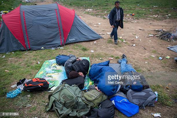 Men sleep on the ground as migrants camp on the forecourt of a petrol station near the Idomeni refugee camp on the Greek Macedonia border on March 17...