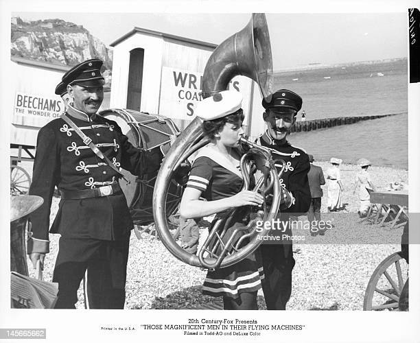 Men smiling as woman plays tuba in a scene from the film 'Those Magnificent Men In Their Flying Machines Or How I Flew From London To Paris In 25...
