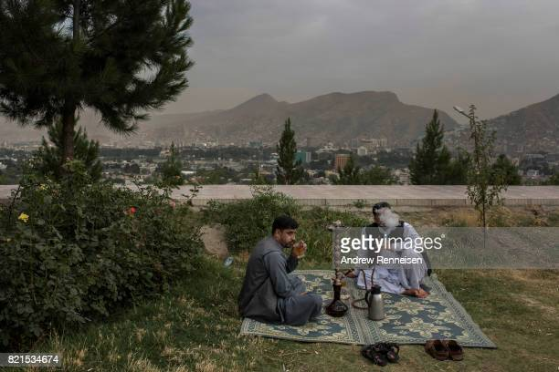 Men smoke a hookah in a park on Wazir Hill on July 19 2017 in Kabul Afghanistan Despite a heavy security presence throughout the city life remains...