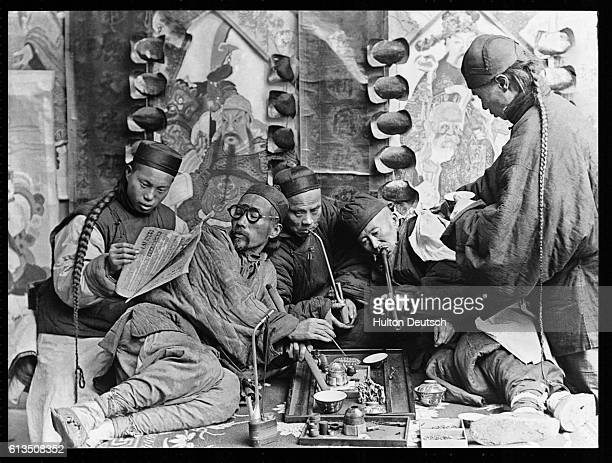 Men smoke pipes and read as they relax inside a Chinese opium den