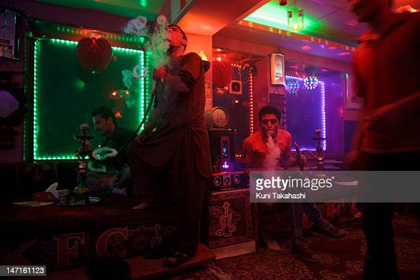 Men smoke shisha or water pipes at cafe on May 16 2012 in Kabul Afghanistan Shisha cafe is one of the few places Afghans go for relaxation in this...