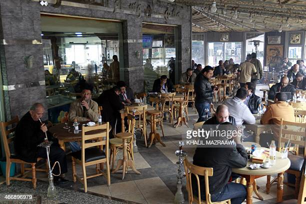 Men smoke water pipes at a cafe in the Jordanian capital Amman on February 3 2014 A ban on water pipes in restaurants and cafes has caused uproar in...