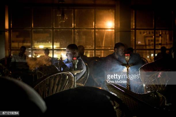 Men smoke waterpipes during a power outage at a cafe in East Mosul on November 5 2017 in Mosul Iraq Five months after Mosul Iraq's secondlargest city...