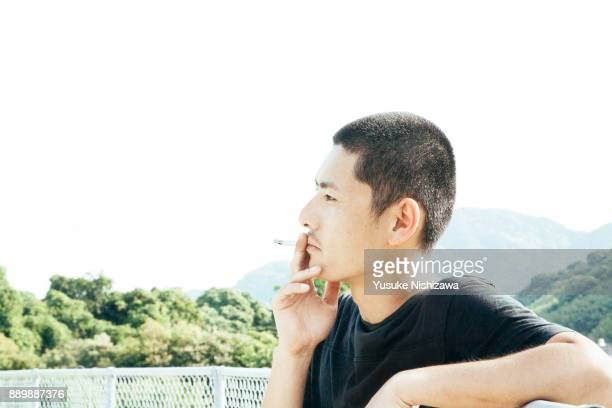 men smoking cigarettes - yusuke nishizawa stock pictures, royalty-free photos & images