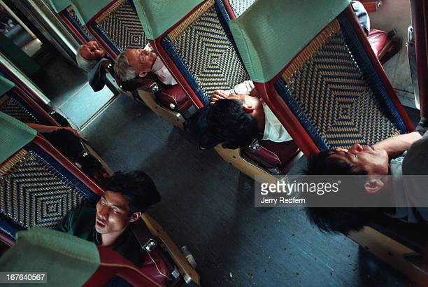 Men snooze on the hard seats of the Reunification Express as it runs from Nha Trang to Hue