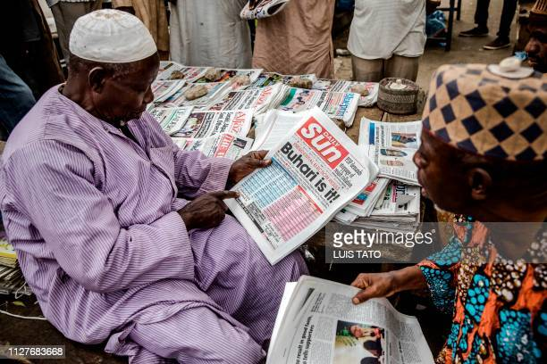 Men speak the news while reading national newspapers with headlines announcing the victory of the incumbent President Muhammadu Buhari following...