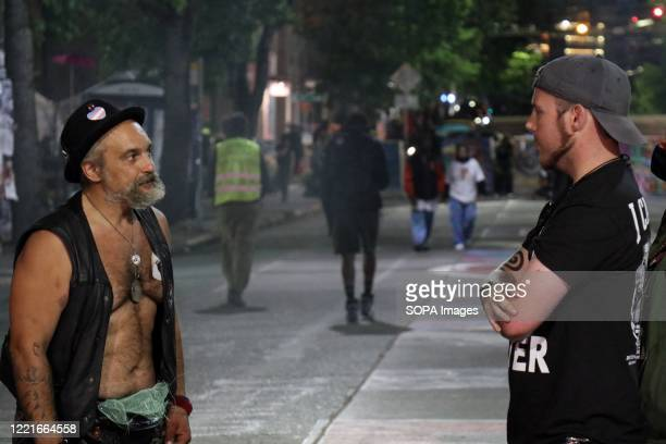 Men speaking along side the street in the Seattles so-called Capitol Hill Autonomous Zone, or CHAZ - an area protesters have taken over after police...
