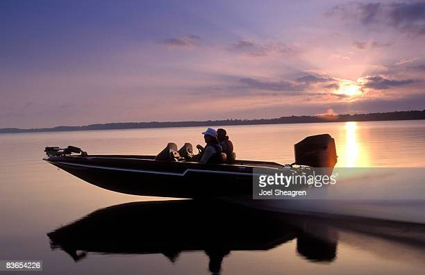Men speed across open water in a boat.