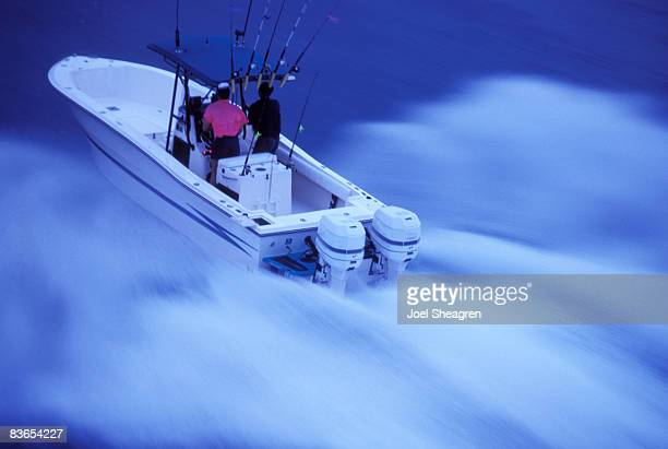 Men speed across open water in a boat.