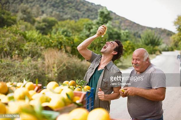 men squashing oranges - greece stock pictures, royalty-free photos & images