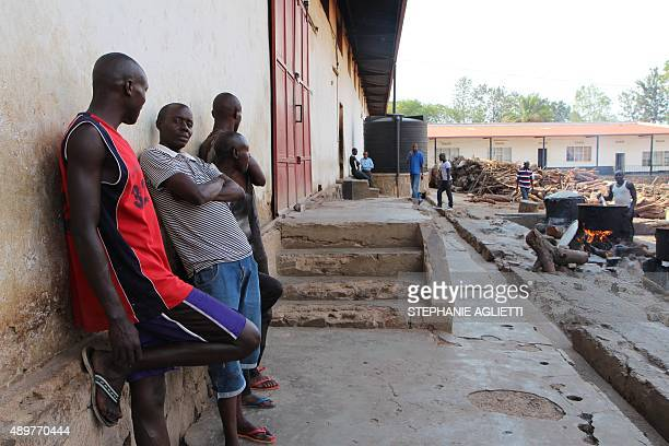 Men stand against a wall at the Gikondo transit center in Kigali on September 24 2015 Rwanda's government was accused on September 24 by rights group...