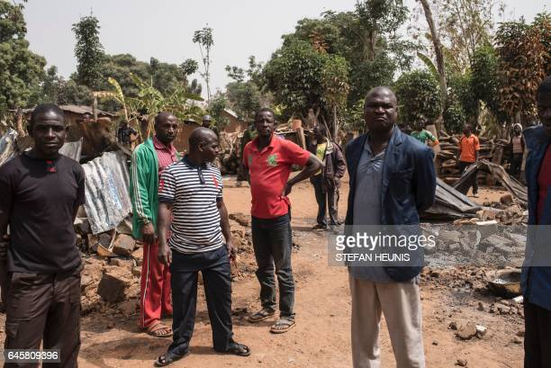 Men stand among rubbles in the village of Bakin Kogi in Kaduna state northwest Nigeria that was recently attacked by suspected Fulani herdsmen on...