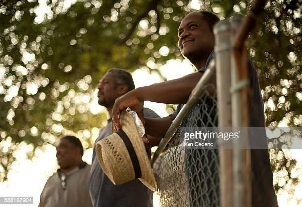 Men stand at the fence during St Paul Church of God in Christs tent revival in the lower 9th ward of New Orleans July 15 2010 Five years after...
