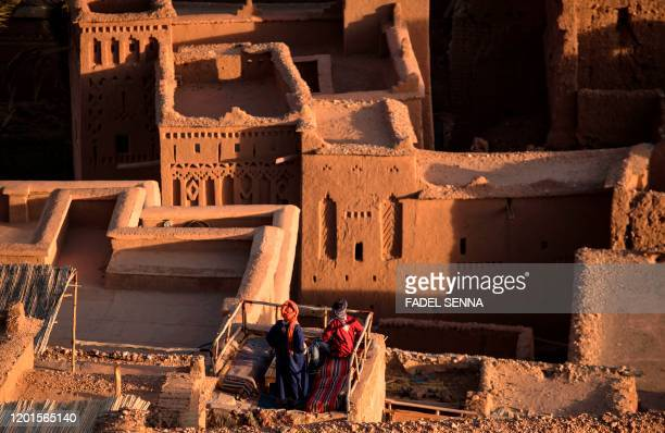 Men stand atop the Kasbah of AitBenHaddou where scenes depicting the fictional city of Yunkai from the hit HBO television series Game of Thrones were...