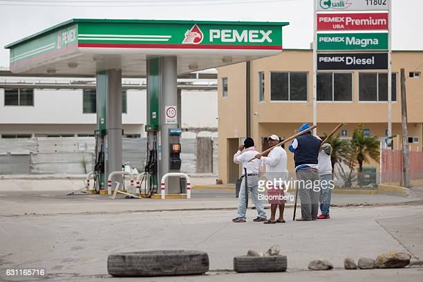 Men stand guard near a Petroleos Mexicanos gas station after looting in Veracruz City Mexico on Saturday Jan 7 2017 Mexico's National Association Of...